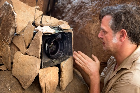 Description: Oliver Goetzl, Field Producer, setting a remote camera in a sloth bear cave.